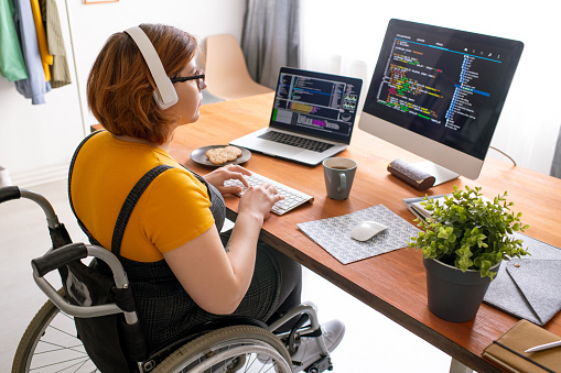 Female freelance programmer in modern headphones sitting in wheelchair and using computers