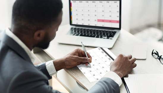 Planning Concept. Black Businessman Using Calendar Program On Laptop And Writing Notes To Planner, Managing His Business Schedule, Checking Events In Organizer, Creative Collage