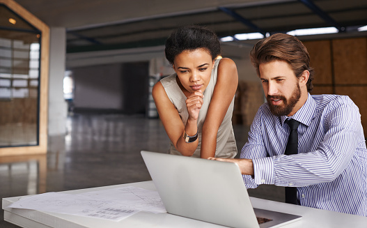 Shot of two architects working together at a laptop