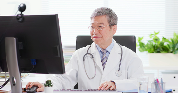 Telemedicine concept - asian male doctor listening to patient talking symptom on the internet